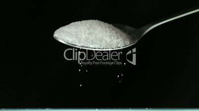 Spoon pouring white sugar on black background