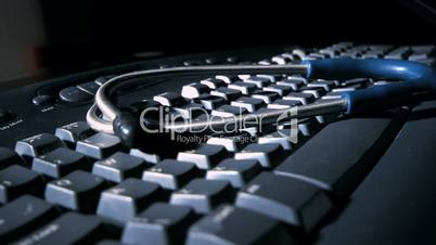 Stethoscope falling onto computer keyboard and bouncing