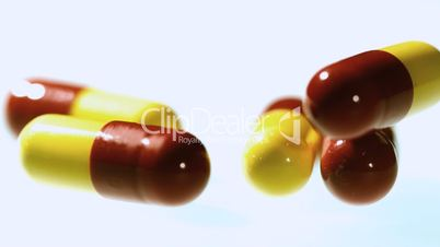 Red and yellow capsule tablets falling and bouncing close up