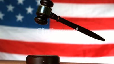 Gavel dropping on sounding block with american flag in background