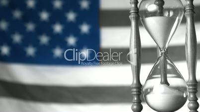 Sand flowing through hourglass with american flag in selective black and white