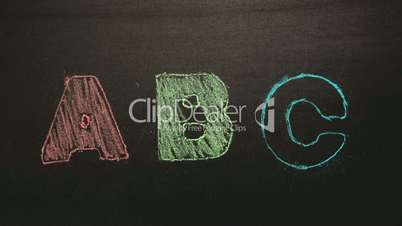 Abc appearing drawn on blackboard with chalk