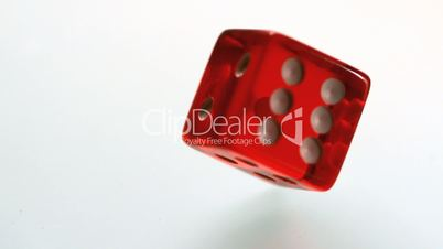 Red dice spinning and settling on white surface