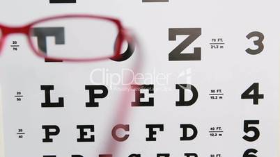 Red glasses held up to read eye test