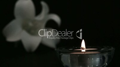 Candle blowing out beside white lily