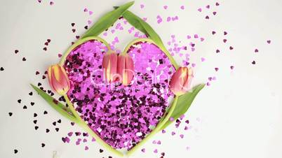Heart made of pink confetti framed by tulips dispersing