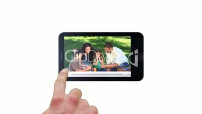 Hand using smartphone screen to press play family clip