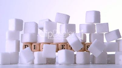 Sugar cubes falling in front of wood dice spelling out diabetes