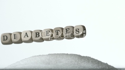 Dice spelling out diabetes falling over pile of sugar on white background