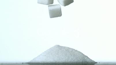 Sugar cubes falling into pile of sugar