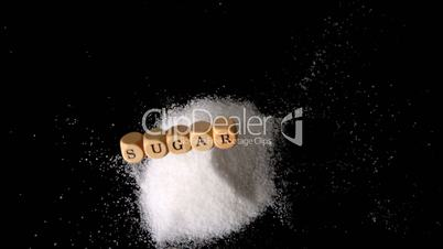 Dice spelling out sugar falling in a pile of sugar