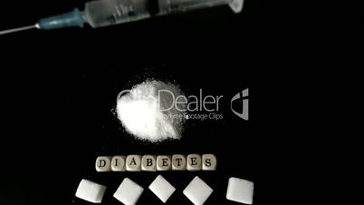 Syringe of insulin falling into pile of sugar next to sugar cubes and dice spelling out diabetes