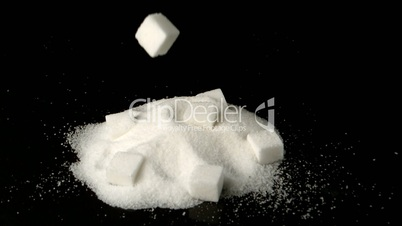 Sugar cube falling in pile of sugar powder