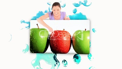 Smiling woman holding a poster of fruits falling into water