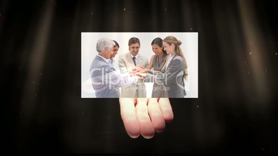Hand showing various screens of people at work
