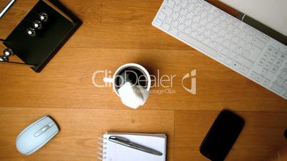 Sugar cubes falling in a coffee cup on a desk