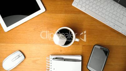 Sugar cube falling into cup of coffee next to tablet pc and smartphone