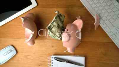 Piggy bank falling on a desk beside tablet pc and keyboard