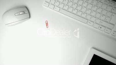 Paperclip falling in the middle of an office desk