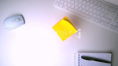 Yellow post it falling on office desk