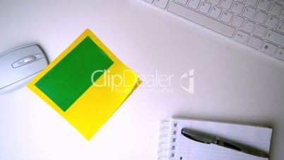 Yellow post it with chroma key falling on office desk