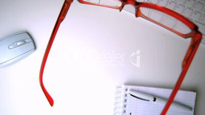 Red glasses falling onto office desk