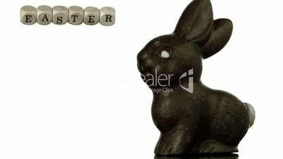 Letters spelling out easter falling beside chocolate bunny