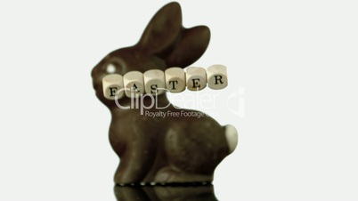 Letters spelling out easter falling in front of chocolate bunny