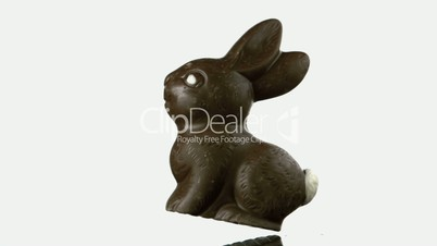 Chocolate rabbit falling and bouncing onto white surface