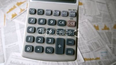 Pocket calculator falling and bouncing on papers