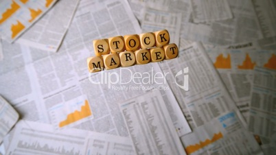 Wooden dice spelling out stock market falling over sheets of paper