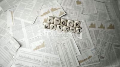 White dice spelling out stock market falling over sheets of paper