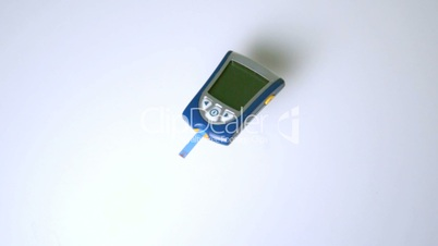 Blood glucose monitor falling on white surface