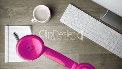 Pink phone receiver falling onto office desk
