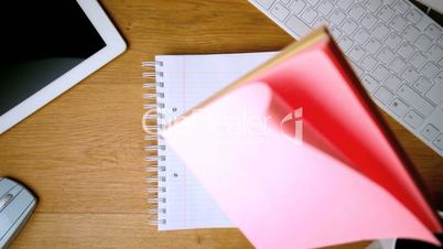 Pink post its falling on notepad on office desk