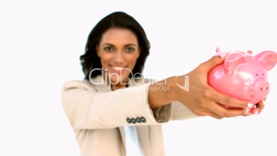 Businesswoman showing piggy bank to the camera
