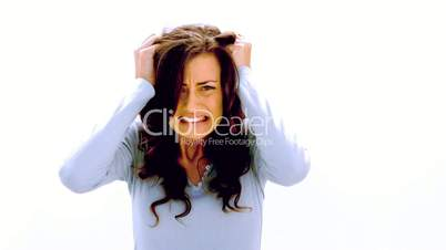 Brunette shaking head and pulling at hair with anger