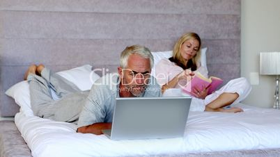 Man lying on his bed with a laptop next to his wife