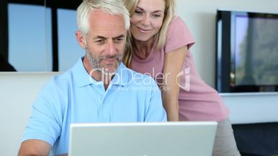 Man using his laptop with his wife