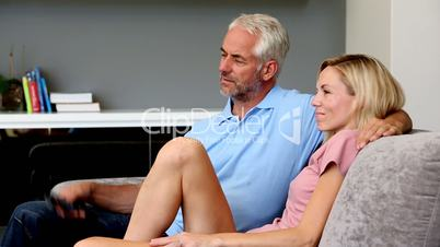 Husband changing channel for his wife
