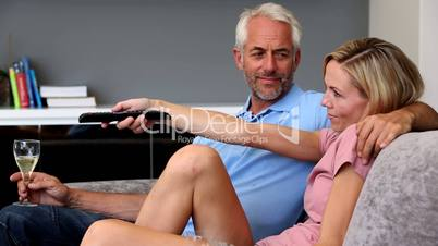 Mature couple watching television in the living room