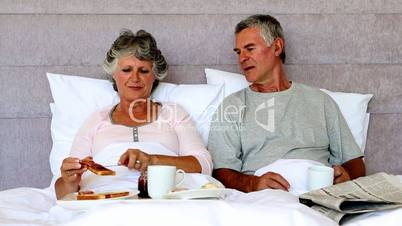 Woman feeding her husband slice of toast