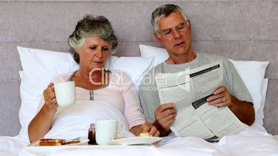 Husband reading the newspaper to his wife during breakfast