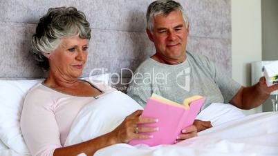 Husband giving a gift to his wife while she is reading a book