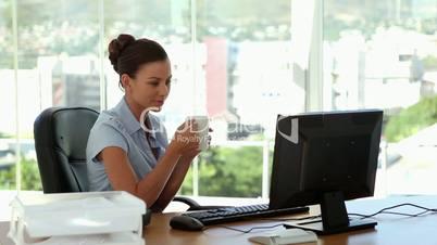 Businesswoman drinking cofffee at her desk