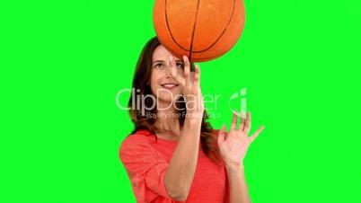 Woman having fun with a basket ball on green screen