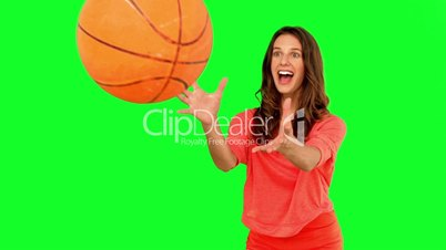 Cheerful woman catching a basketball on green screen
