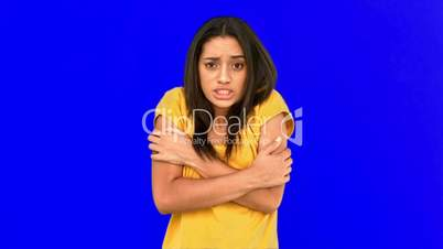 Woman shivering with cold on blue screen