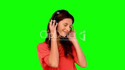 Woman with headphone listening to music on green screen