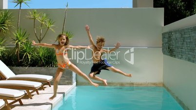 Brother and sister diving into the swimming pool